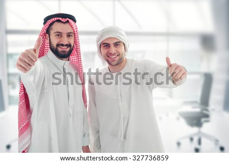 Arabian businessmen in a modern interior, thumbs up, success concept - stock photo