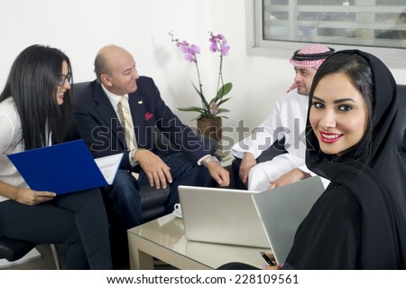 Arabian Businesswoman in office with Businesspeople meeting in the background, Arabian woman wearing Hijab in office with her colleagues in background - stock photo
