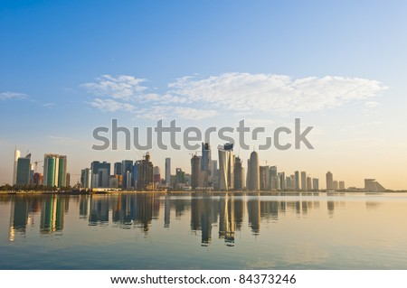 Arabian city of Doha Qatar, where the skyline changed drastically over the past 5 years. Image captured early in the morning with the sun rising from the right and some rare fluffy clouds in the sky.. - stock photo