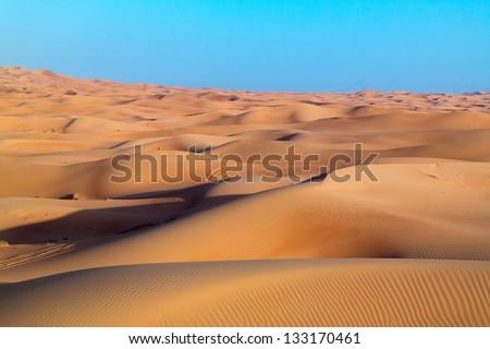 Arabian desert dune background on blue sky. Desert near the city of Dubai. desert landscape. dunes stretching into garizont - stock photo