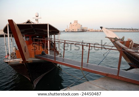 Arabian dhows tied up in Doha Harbour, with Qatar's Museum of Islamic Art in the background. Qatar is seeking to establish itself as a major  centre of Arab culture. - stock photo