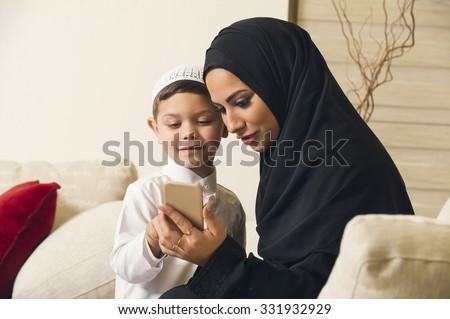 Arabian family, Arabian mother and son using mobile phone - stock photo