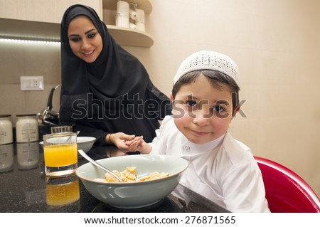 Arabian family of mom and son having breakfast in the kitchen  - stock photo
