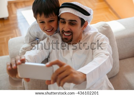 Arabian Father And Son Relaxing At Home Using a Smartphone At Home - stock photo
