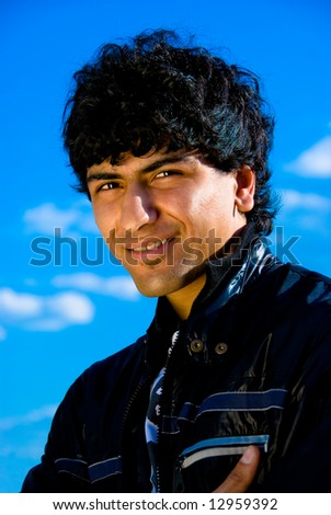 Arabian guy portrait over blue sky background - stock photo