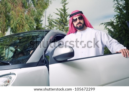 arabian guy posing against his car at home - stock photo