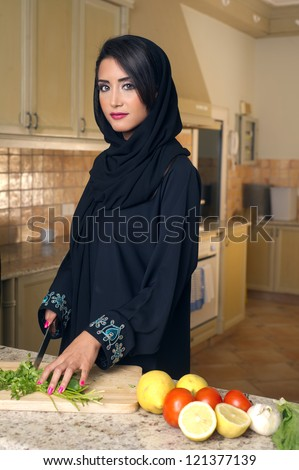 Arabian lady wearing hijab cutting veggies in the kitchen - stock photo