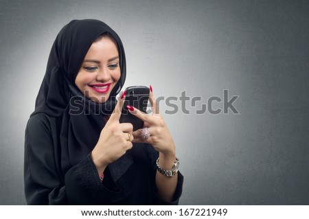 Arabian lady wearing hijab using her mobile isolated - stock photo
