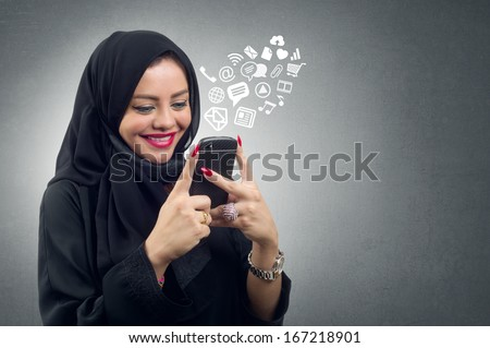 Arabian lady wearing hijab using her mobile with virtual apps icons  - stock photo