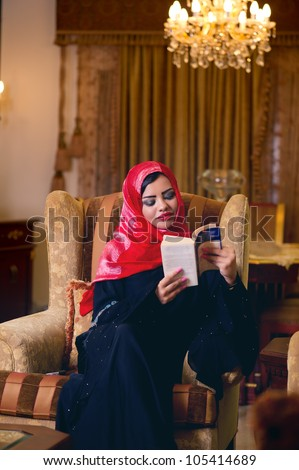 arabian lady with hijab relaxing at her home reading a book - stock photo