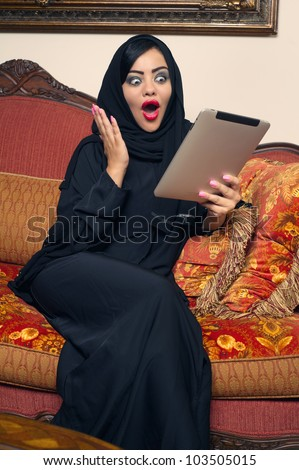 arabian lady with hijab shocked while using a Pad - stock photo