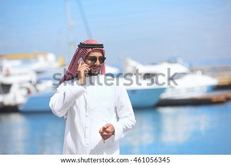 Arabian man talking on the cell phone at the yacht harbor