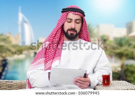 arabian man working on a mobile tablet & drinking tea - stock photo