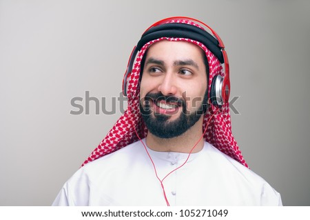 Arabian middle eastern guy with headphones enjoying music - stock photo