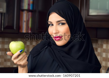 Arabian woman holding an apple in the kitchen - stock photo