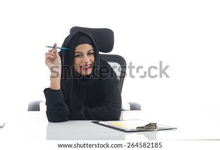Arabian woman in her office with a cheerful expression - stock photo
