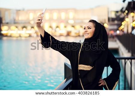 Arabian woman taking selfie. - stock photo