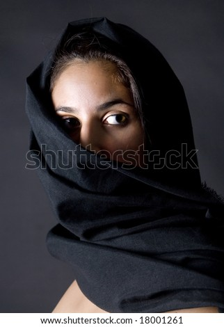 arabian woman with black vell in black background - stock photo