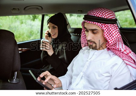 Arabic Businessman And Businesswoman Traveling In The Car Using Technology - stock photo