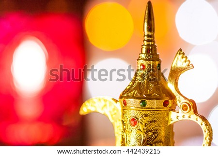 Arabic Coffee pot and lantern with colorful out of focus light as background. Ramadan, Eid Mubarak concept - stock photo