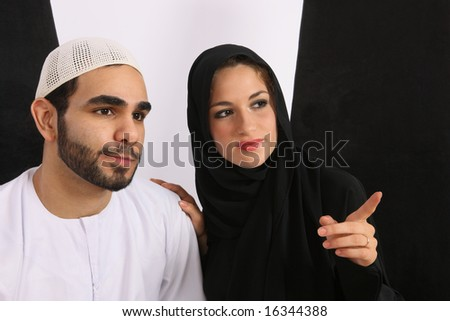 Arabic Couple Looking In Amusement - stock photo