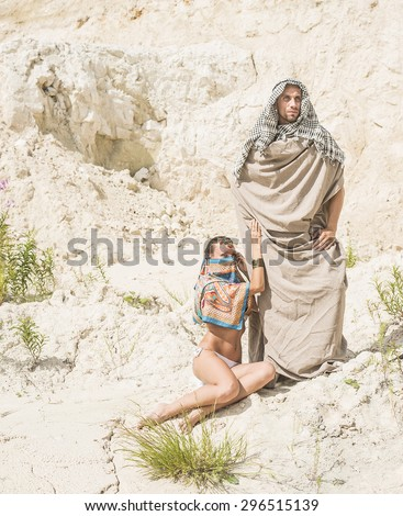 Arabic Couple muslim Looking at camera Arab man and woman in white sand desert against dry desert Empty space for inscription Young rich family  - stock photo