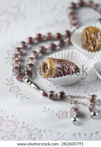 Arabic dates arranged in white paper cups with islamic prayer beads. Ramadan objects. - stock photo