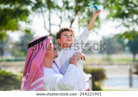 Arabic father and little kid play outdoors. - stock photo