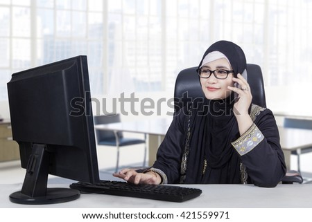Arabic female entrepreneur talking on the mobile phone while working with a computer in the office - stock photo