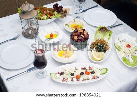 Arabic food of dates, hommos, cheese, labneh and fattoush served in Ramadan  - stock photo