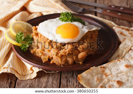 Arabic ful medames with a fried egg and bread close-up on the table. horizontal - stock photo