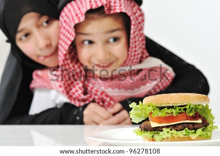 Arabic girl and boy with big Burger - stock photo