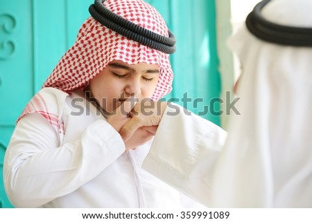 Arabic kid kissing parent for traditional act of respect