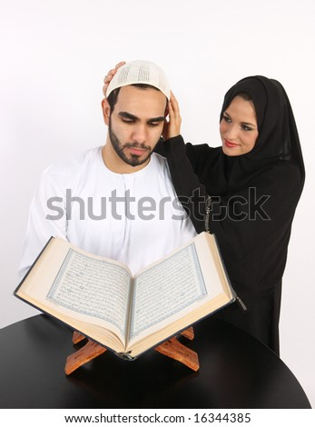 Arabic Loving Wife Adjusts Husbands Prayer Cap As He Recites The Holy Quran - stock photo