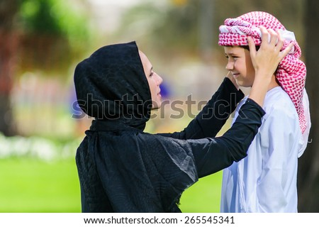 Arabic mother and son outdoors. - stock photo