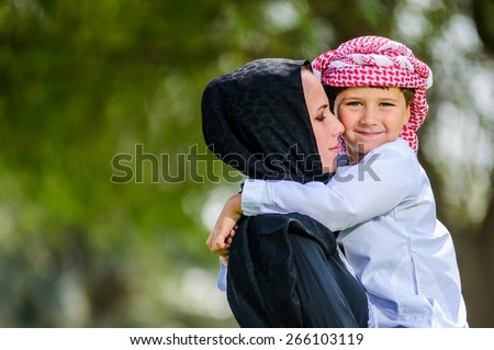 Arabic mother and son outdoors.Middle East. - stock photo