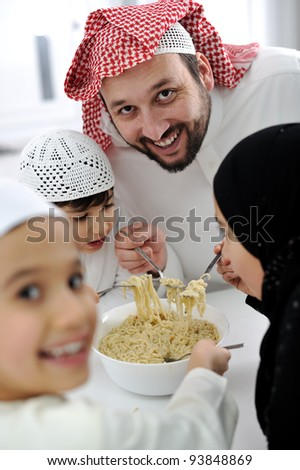 Arabic muslim family eating  at home together, father and kids - stock photo