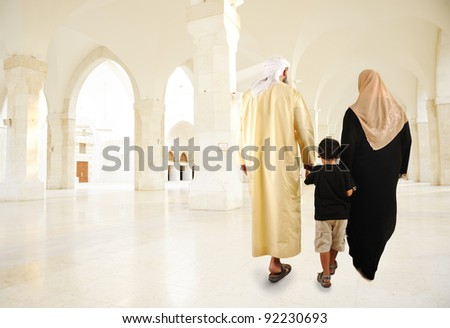 Arabic Muslim family walking indoor - stock photo