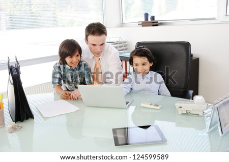 Arabic Muslim father teaching his sons in office - stock photo