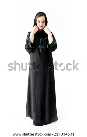 Arabic Muslim girl wearing black robe over white background posing - stock photo