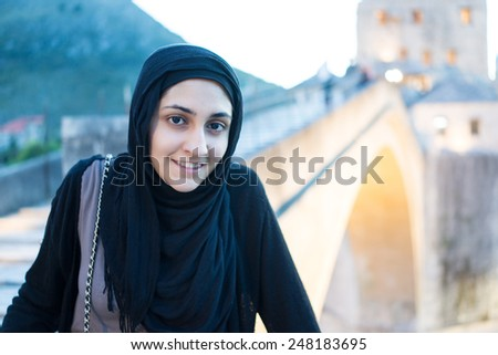 Arabic Muslim Middle Eastern girl traveling for vacation in Mostar bridge - stock photo
