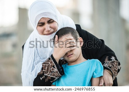 Arabic Muslim Middle Eastern woman with olive branch and son crying - stock photo