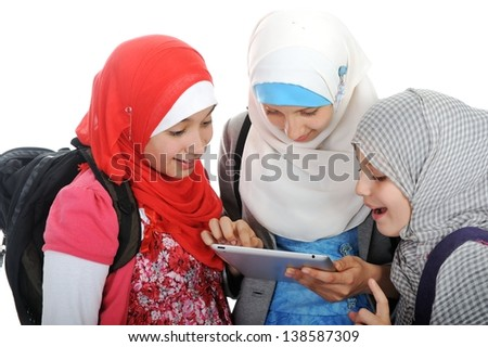 Arabic Muslim school girls working together on tablet pc - stock photo