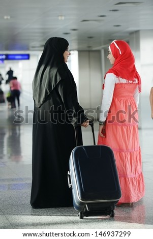Arabic Muslim teenage girl traveling with her mother, airport transit - stock photo