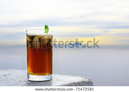 Arabic nana mint tea in traditional glass with foggy landscape on background: sea mountain and clouds