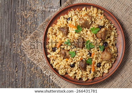 Arabic national rice food called pilaf. Served in clay bowl on wooden table background.  Cooked with fried meat, onion, carrot and garlic - stock photo