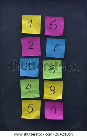 arabic numerals from zero to nine handwritten on colorful crumbled sticky notes and posted on blackboard with eraser smudges