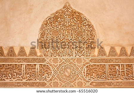 Arabic stone carvings on a wall in the Nasrid Palaces of the Alhambra of Granada, Spain.