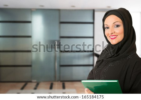 Arabic woman, traditional dressed, standing in front of the office. - stock photo