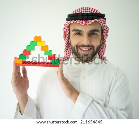 Arabic young businessman building cube house - stock photo
